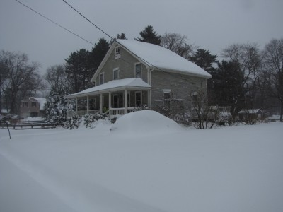 the house and car in the blizzard, the latter covered with snow
