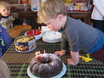 Lijah blowing out the second of his three candles