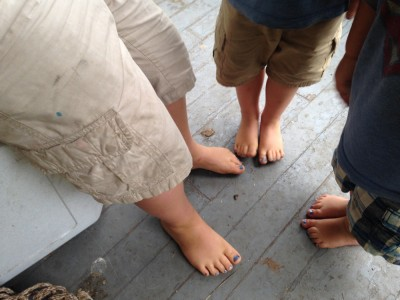 the three boys' feet, with blue-painted toenails