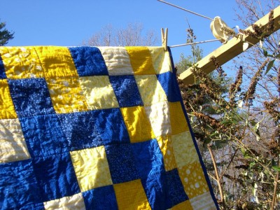 blue and yellow quilt hanging on the line