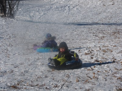 Zion and Nisia going down the hill in snowtubes