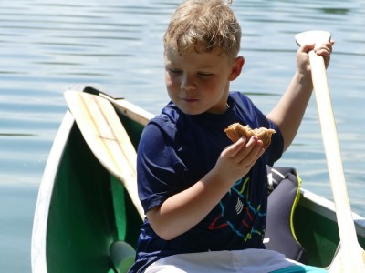 Zion eating a sandwich sitting in the canoe