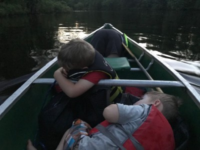 the kids lying down in the canoe