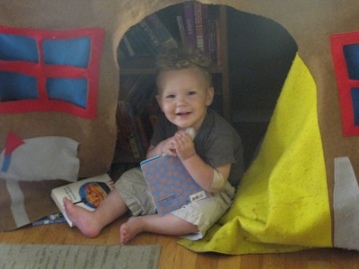 Lijah in the playhouse looking at a book