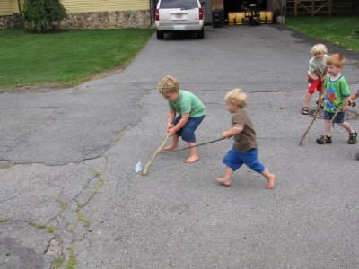 Harvey, Zion, and the other kids batting a bottle around the street with sticks