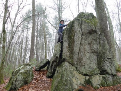 Elijah climbing up the side of a large boulder or outcropping