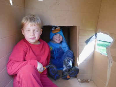 Zion and Lijah inside a cardboard box house