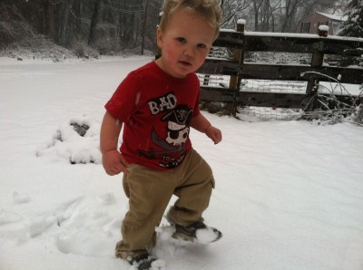 Lijah walking in the snow in a short sleeve shirt and Zion's sneakers