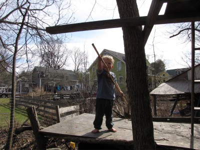 Lijah on a treehouse holding a stick in a warlike posture