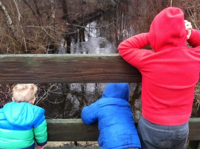 the three boys on the road bridge looking down on the rain-swollen brook