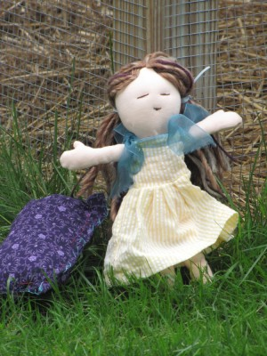 a doll with brown hair and a yellow dress, with her purple pillow