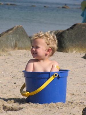 Lijah sitting in a big blue bucket on the beach