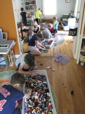 kids building with lots of legos on the living room and playroom floor