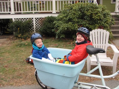 Harvey and Zion in the back of the big bike, well bundled up, outside our house