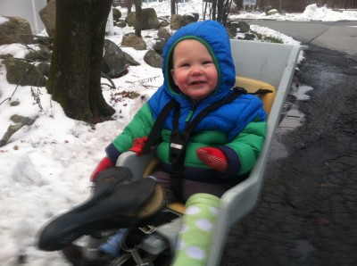 Lijah in winter gear and silly leg warmers in the bike seat