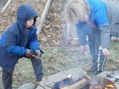 Havrvey and Zion toasting marshmallows in winter coats (and bare feet)