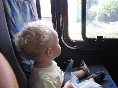 Lijah sitting in his own seat on the bus, looking out the window