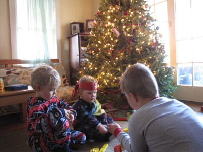 the boys in pjs playing in front of the Christmas tree
