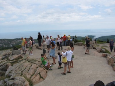 lots of people wandering around on a paved area atop Cadillac Mtn