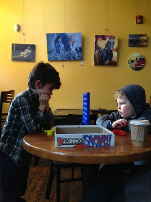 Hendrick and Harvey playing Connect-4 in a hip cafe