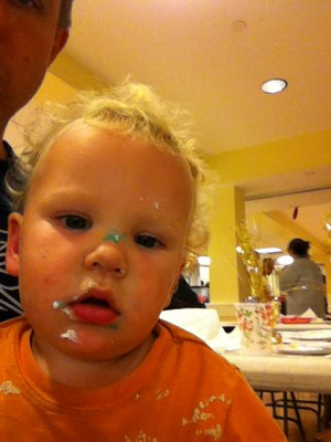 Lijah with white and blue frosting spotted all over his face