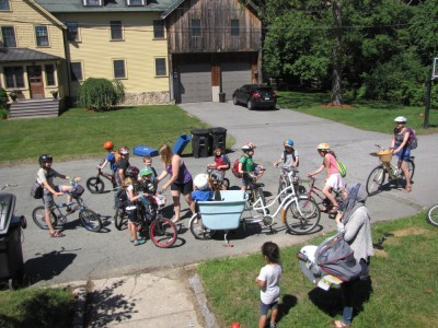 a crowd of kids stradling bicycles ready to ride