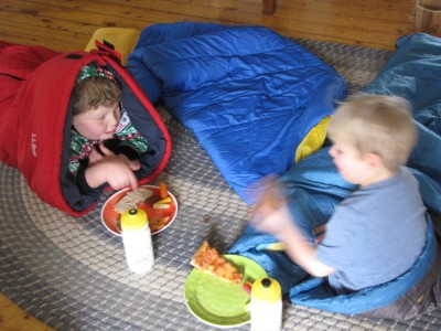 Harvey and Zion in their sleeping bags in the living room eating lunch