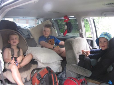 the boys in their car seats amidst the camping gear