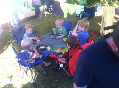all five of the little kids eating pasta at the low table