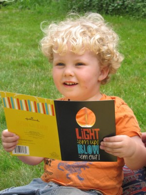 Harvey holding a musical birthday card with a spinning candle flame