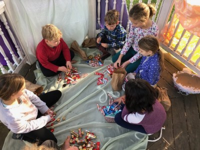 kids sitting in a gazebo with piles of candy