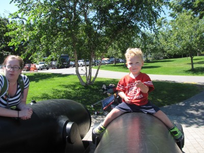 Lijah astride a giant cannon, Zion and Nathan lying down in the background