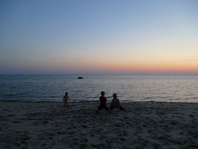 the boys playing on the beach at dusk