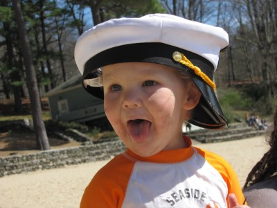 Lijah at the beach with Harvey's captain hat on