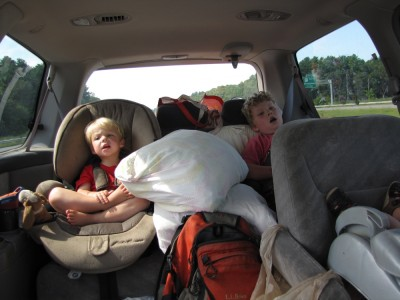 Zion and Harvey comfy among camp supplies in the back seat, singing