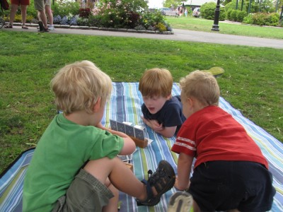 Zion and Nathan playing cards on a picnic blanket, Lijah looking on