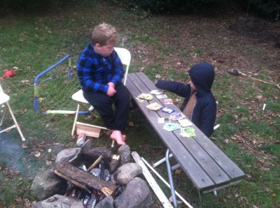 Harvey and Zion looking at Pokemon cards by the fire