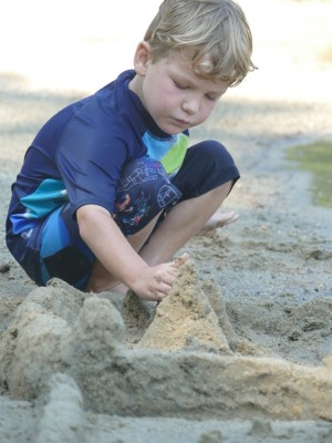 Elijah concentrating on building a sandcastle