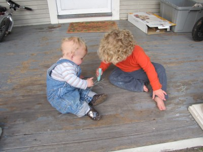 Zion and Harvey drawing with chalk on the porch