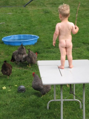 Naked Lijah standing on top of a table on the lawn, holding a stick, watching the chickens