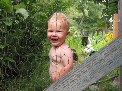 naked Lijah smiling bihind a chickenwire gate