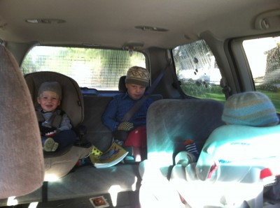 the boys in their car seats wearing winter hats