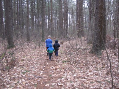 the boys walking in the woods with Rascal wearing warm clothes