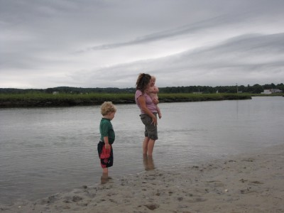 Harvey, and Leah holding Zion, wading in the gray water