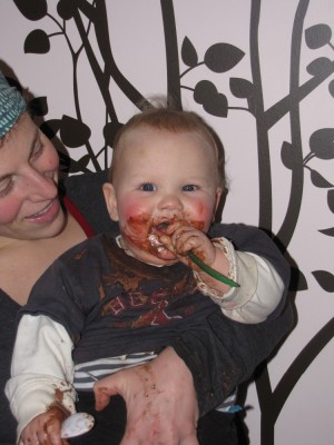 Lijah with chocolate pudding all over his face and clothes, held by Mama