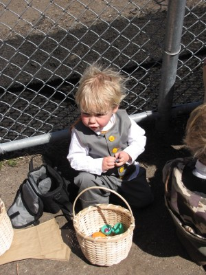 Zion leaning against a fence opening eggs and eating chocolate