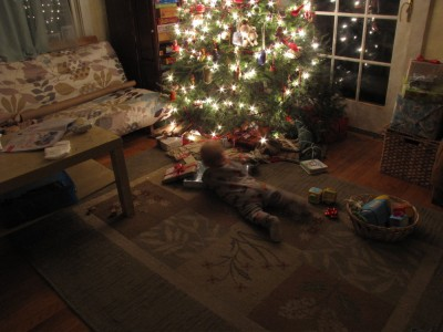 Lijah playing with presents in front of the Christmas tree