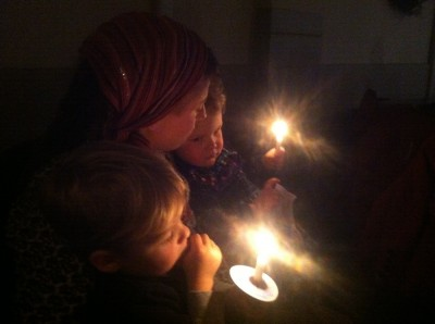 Mama, Zion, and Lijah cuddling by candlelight at church