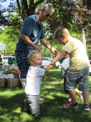 three boys playing ring-around-the-rosie with Grandpa at the farmers market