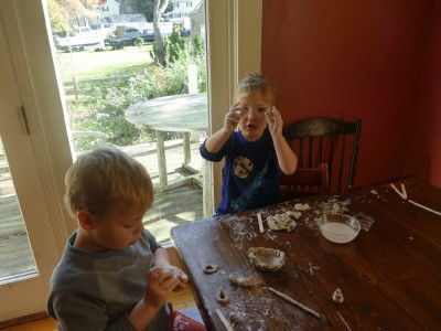Lijah and Zion working with clay at the kitchen table